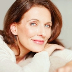 Portrait of a smiling middle aged brunette relaxing on couch
